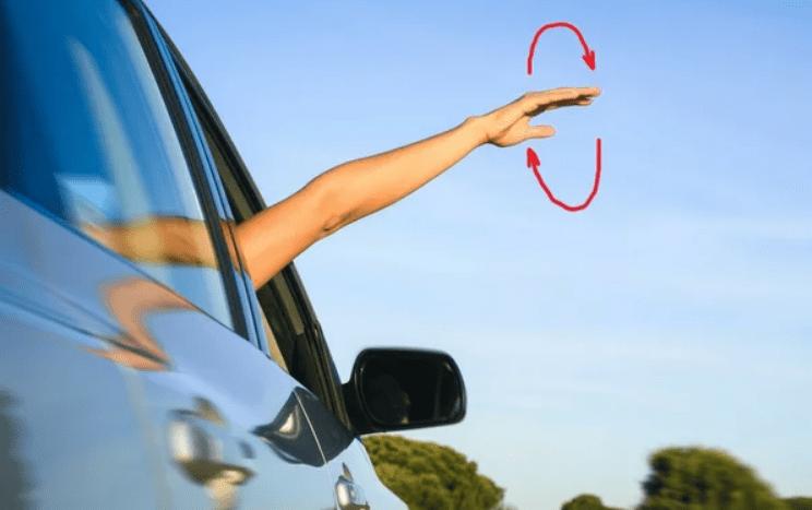 Водитель чертит рукой круг