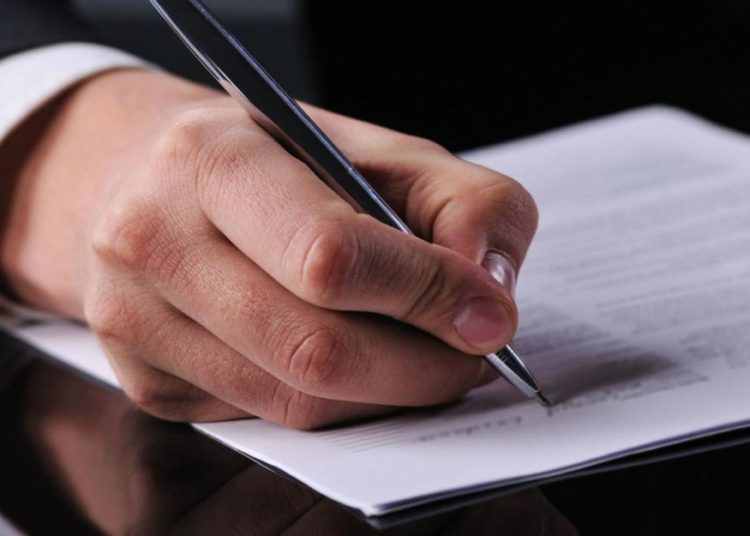 Человек заполняет документ