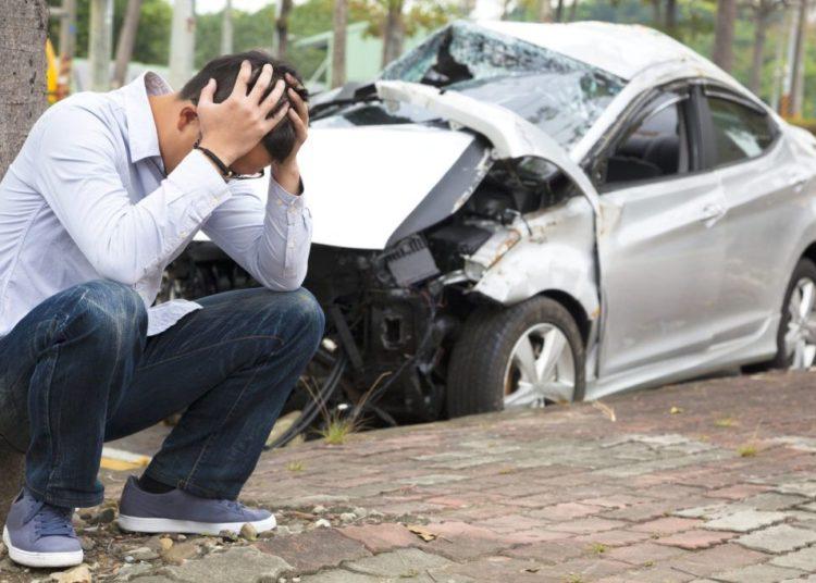 Человек держит руками голову и разбитое авто