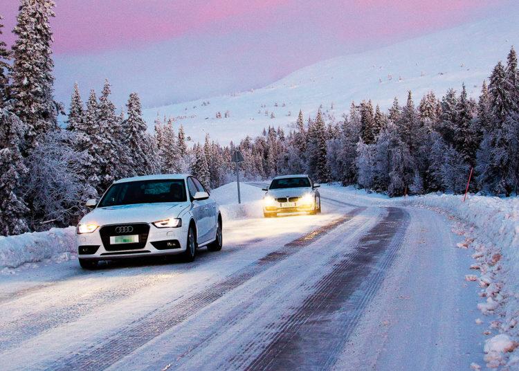 Машины с включенными фарами по снегу