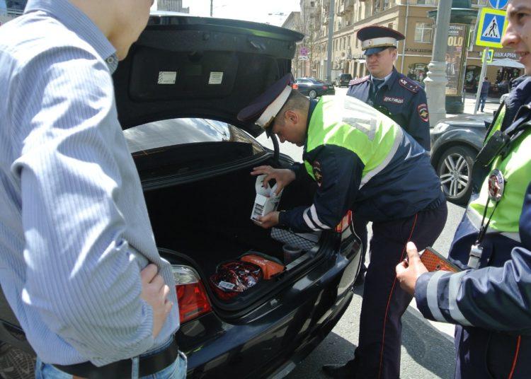 Гаишник обыскивает багажник авто