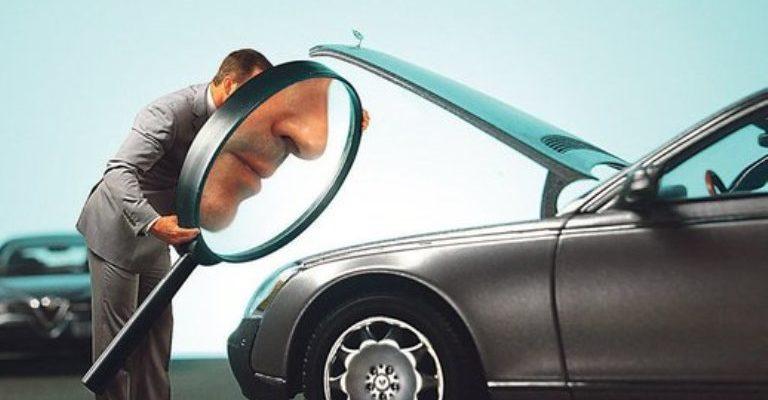 Мужчина смотрит на авто через лупу