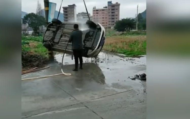 Мужчина моет подвешенную машину