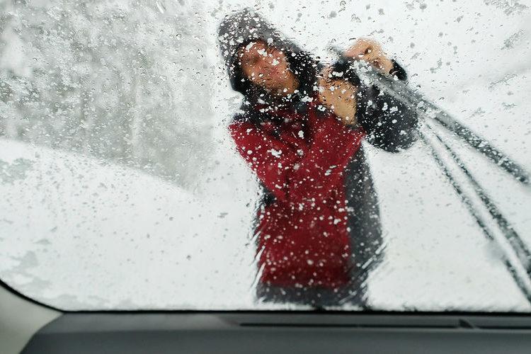 Человек очищает дворники на авто от снега