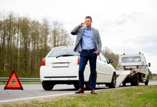 Знак аварийной остановки и водитель с телефоном