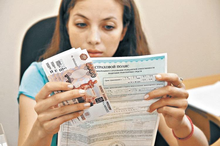 Девушка держит страховой полис и деньги
