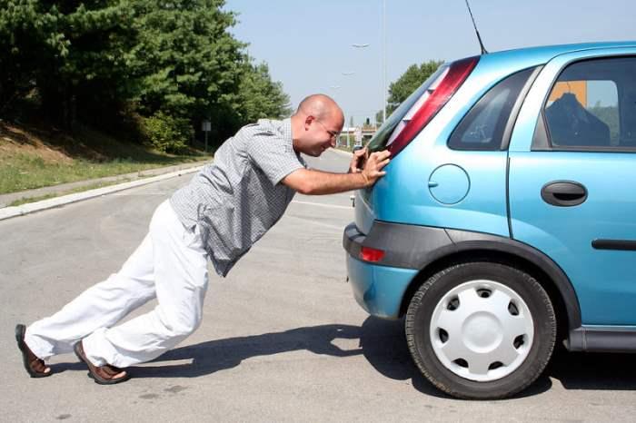 Мужчина толкает авто