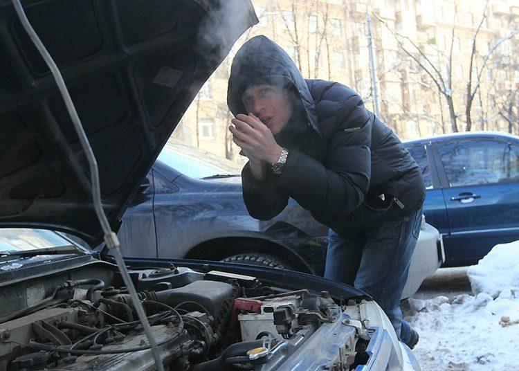 Мужчина греет руки возле авто