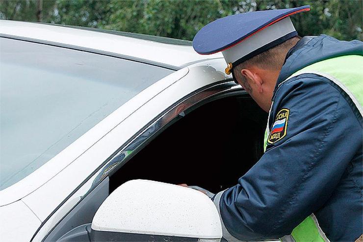 Сотрудник ДПС заглядывает в авто