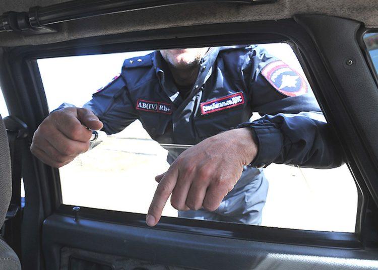 Сотрудник ДПС заглядывает в окно авто