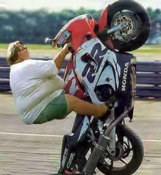 Полная женщина на мотоцикле на задних колесах