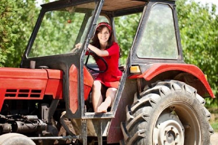 Молодая девушка на тракторе