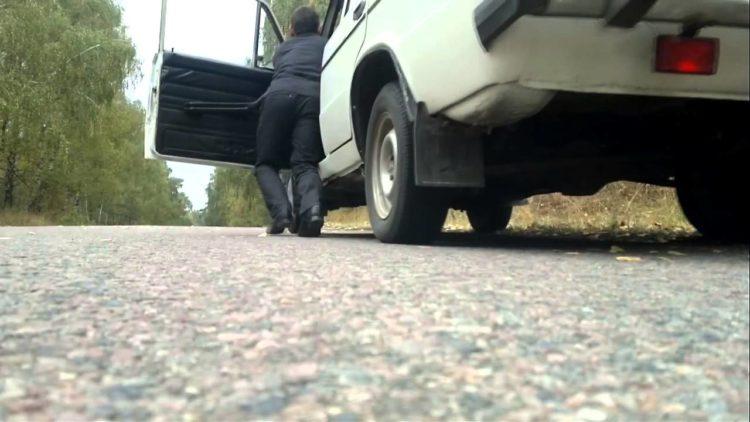 Водитель заводит авто с толкача