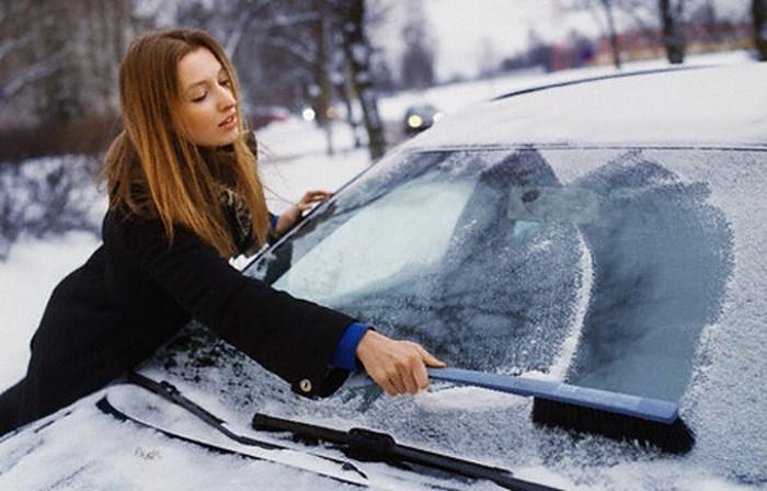 Девушка чистит лобовое стекло от снега