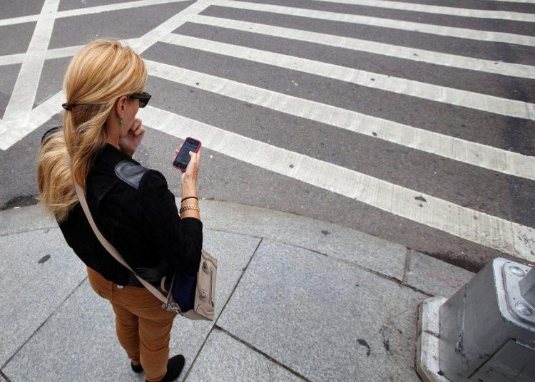 Девушка с телефоном на пешеходном переходе