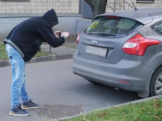 Мужчина фотографирует номер авто