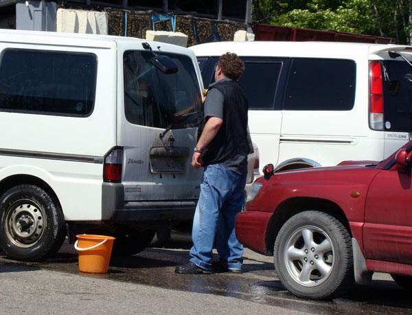 Водитель моет авто на дороге