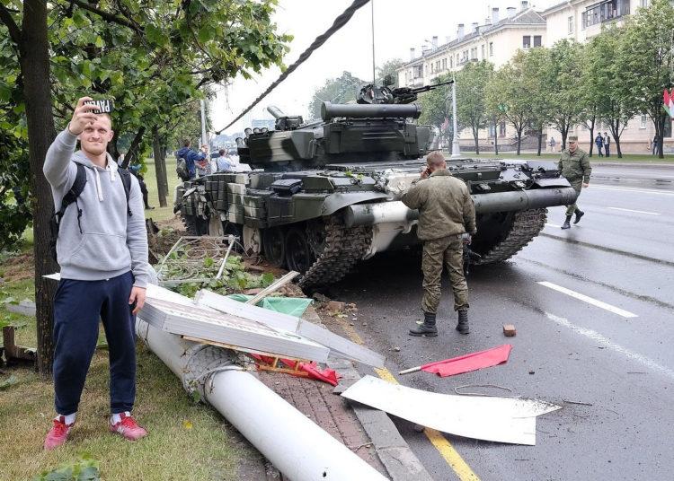 Человек фотографирует аварию с танком