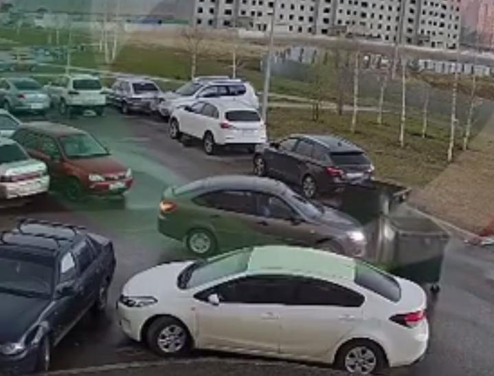 Мусорный бак возле капота автомобиля