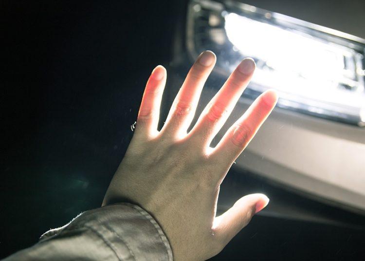 Рука закрывает фару