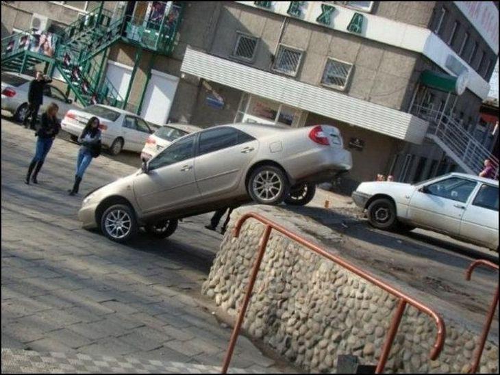 Авто задними колесами на парапете