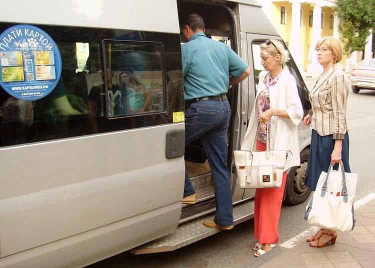 Люди заходят в автобус