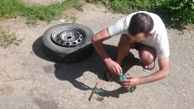 Мужчина открывает бутылку и колесо