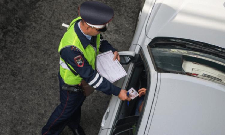 Инспектор ГИБДД передает документ водителю