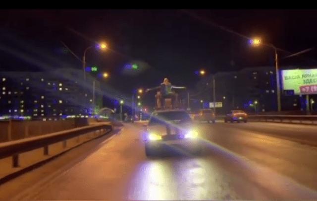 Человек едет на крыше автомобиля