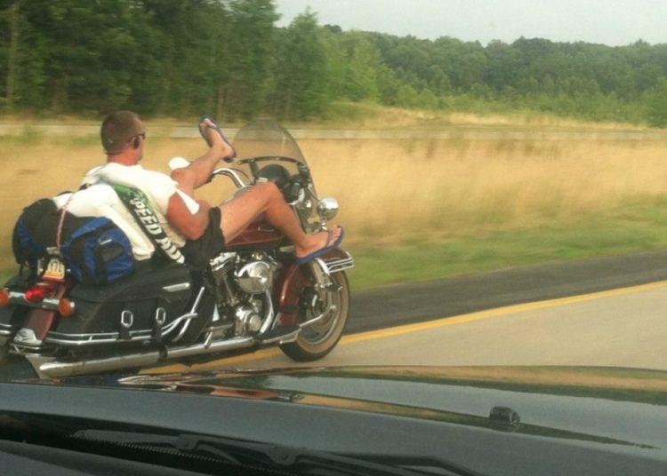 Человек поднял ноги на мотоцикле