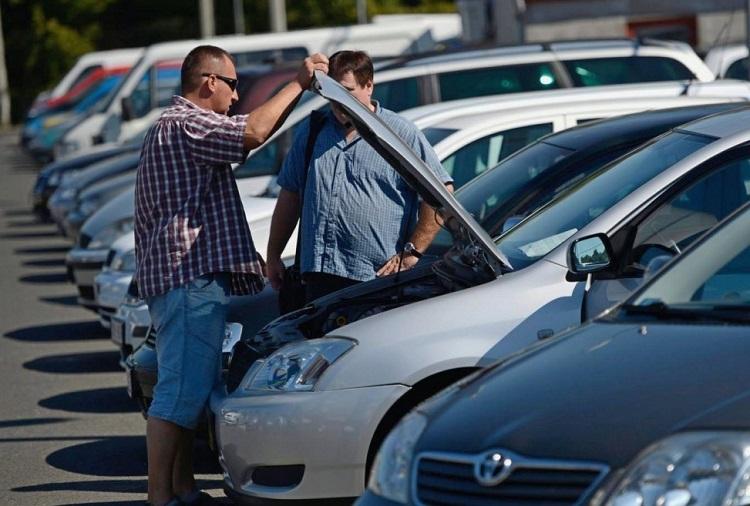 Мужчины смотрят под капот автомобиля