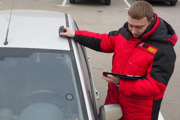 Мужчина с документом возле автомобиля
