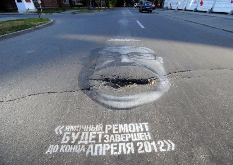 Лицо чиновника вокруг ямы на дороге