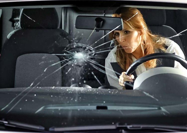 Водитель смотрит на разбитое стекло