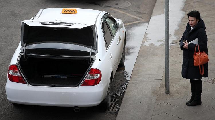 Такси и девушка на тротуаре с телефоном
