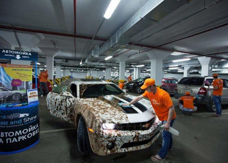 Человек моет грязный автомобиль
