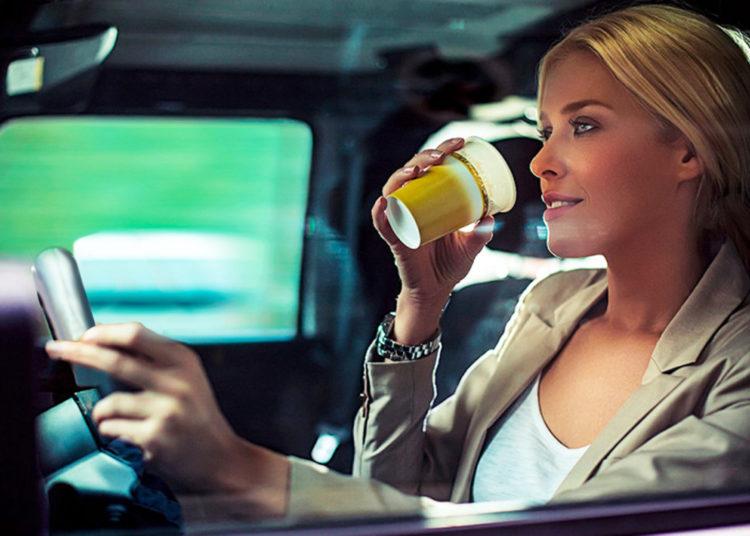 Женщина за рулем с кофе