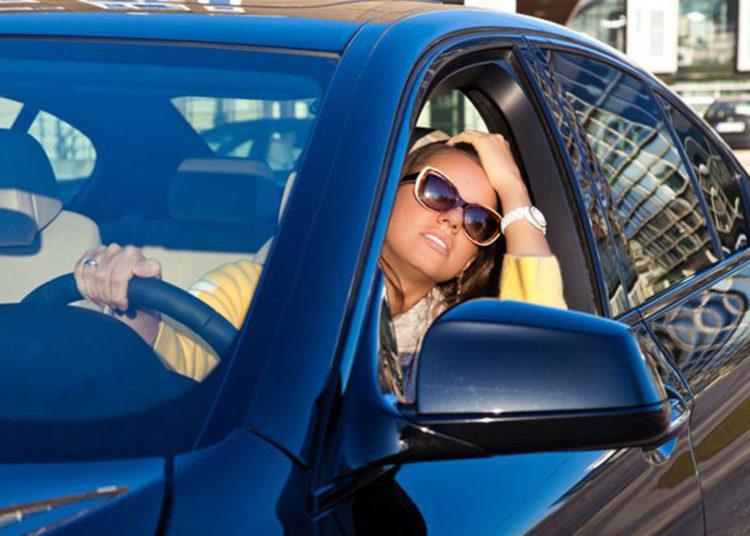 Девущка-водитель выглядывает в окно