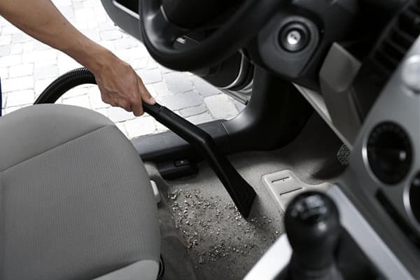 Уборка пылесосом пола автомобиля