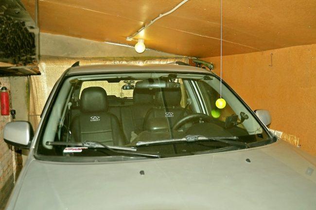 Автомобиль и висящий теннисный мячик в гараже