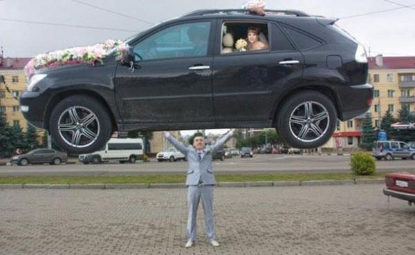 Жених держит свадебную машину