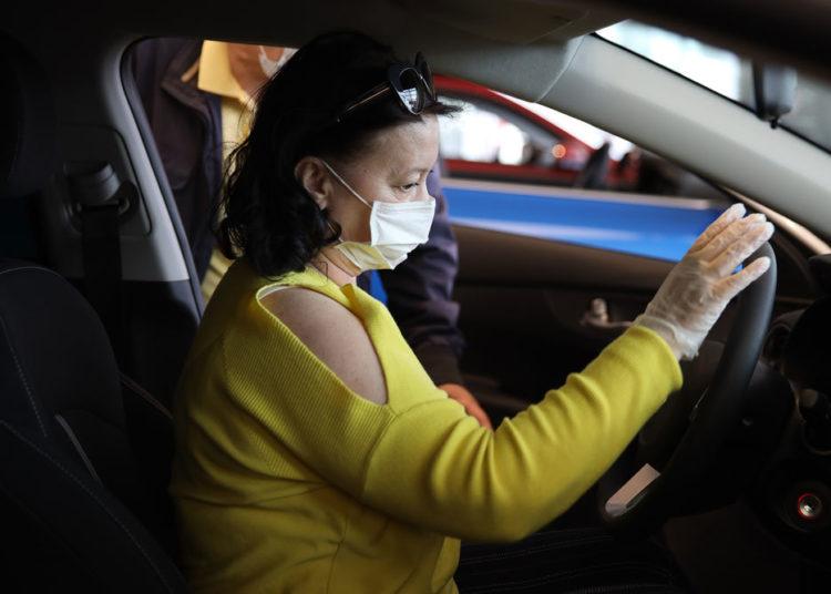 Женщина в маске и перчатке за рулем