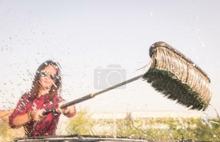Девушка щеткой моет стекло машины