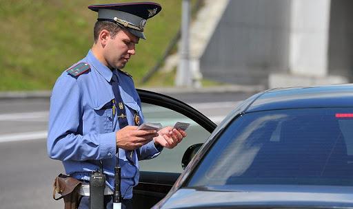 Сотрудник ГИБДД возле машины