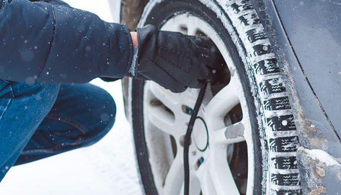 Человек накачивает колесо зимой