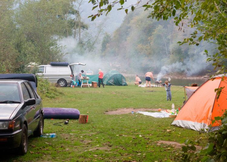 Палатки и машины возле реки на траве