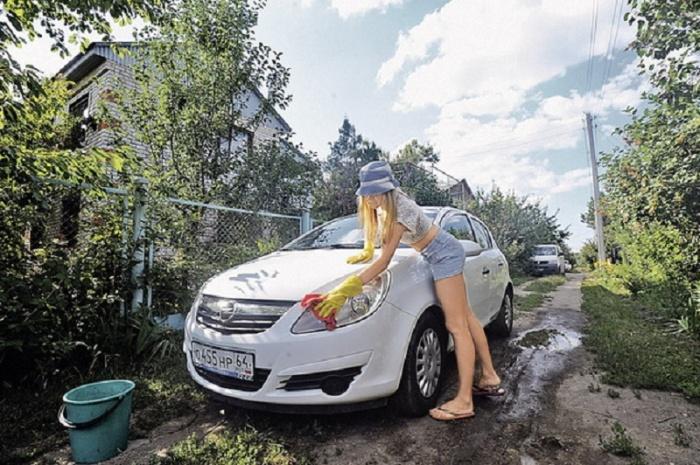 Девушка моет авто на проселочной дороге