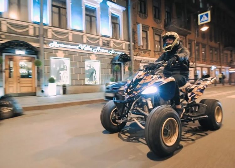 Водитель на квадроцикле на городской дороге