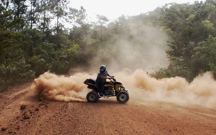 Квадроцикл в пыли на лесной дороге