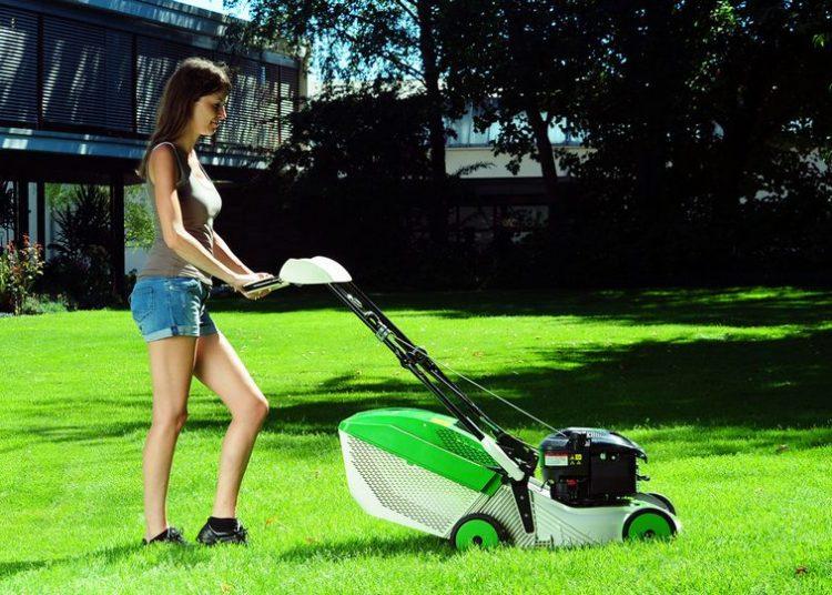 Девушка косит траву газонокосилкой